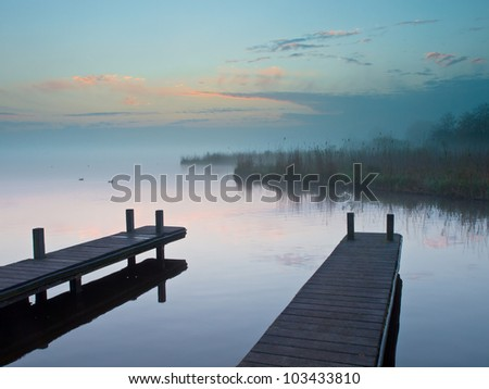 Two jetties at a misty lake during sunrise