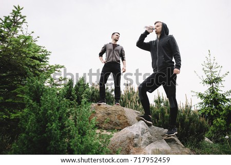 Two joggers are standing on the top of the hill and having some rest after a long running. One of them is drinking water from the bottle while the other one is resting and looking somewhere aside. #717952459