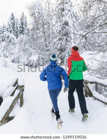 two joggers running in fantastic wintry landscape #1249519036