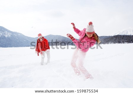 Two joyful and energetic friends playing games and having fun, having a snow ball fight in the snow mountains landscape during a skiing holiday on a sunny winter day, outdoors.