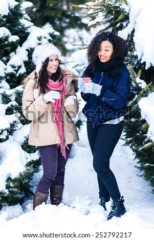 Two joyful and energetic friends playing games and having fun, having a snow ball fight in the snow mountains landscape during a skiing holiday on a sunny winter day, outdoors. snowballs