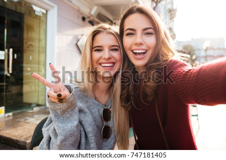 Two joyful attractive girls taking a selfie while sitting together at cafe and showing peace gesture outdoors