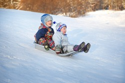 Two joyful childred sledding down the hills on a winter day.