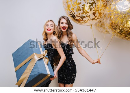 Two joyful fashionable young women in luxury black dresses celebrating birthday party on white background.Having fun, elegant look, smiling, true emotions.Holding big present, golden balloons, tinsels
