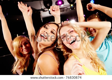 Two joyful girls dancing in night club and having fun