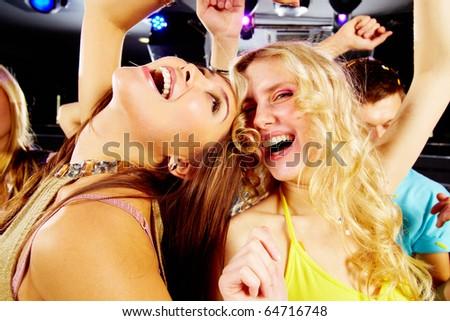 Two joyful girls laughing in night club at disco