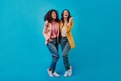 Two joyful girls posing on blue studio background. Full length photoshoot of stylish female models.