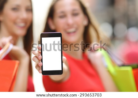 Two joyful shoppers with shopping bags showing a blank smart phone screen in the street