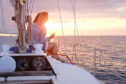 Two joyful women are celebraiting good summer day at the yacht while watching beautiful sunset.