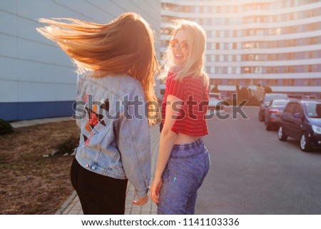 Two joyful women  having fun outdoor in sunlight. Windy hairs. Blonde girl turns Around and laughing. Stylish jeans jacket with print. Urban background .