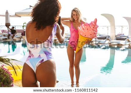 Two joyful young girlfriends taking pictures while posing at the swimming pool resort spa