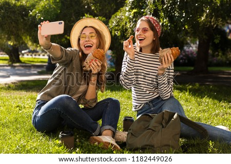 Two joyful young girls friends having fun at the park, taking a selfie, having a picnic