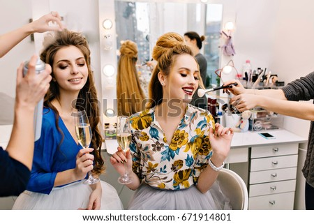 Two joyful young women with luxury look drinking champagne during preparation to party in beauty salon.