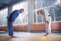Two judo fighters or athletes greeting each other in a bow before practicing martial arts in a fight club. The two fit men in uniform. Fight, karate, training, arts, athlete, competition concept