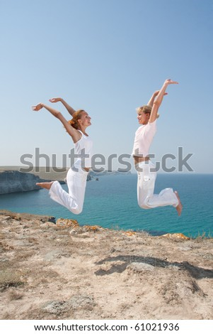 Two jumping women in white cloth against the sea