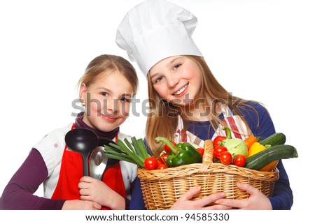 two junior cook with a basket full of vegetables - stock photo