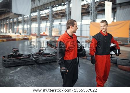 Two kart racers holds hemets, back view #1555357022