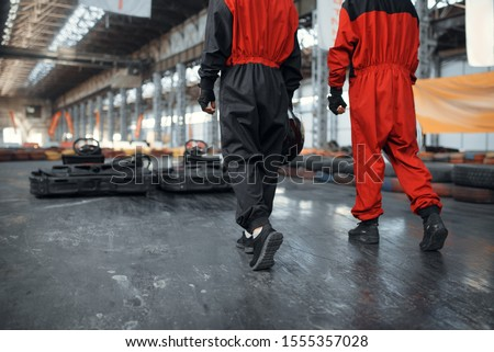 Two kart racers holds hemets, back view #1555357028