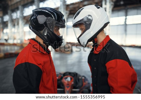 Two kart racers in helmets standing face to face #1555356995