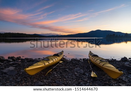 Two kayaks on the shore of a lake during a tranquil dusk. Jamtland, Sweden.