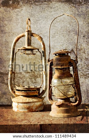Two kerosene lamps on old table  with grunge texture