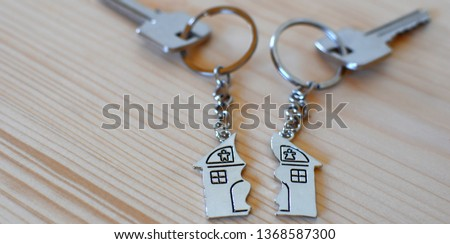 Two keys with splitted broken key rings with pendant in shape of house divided in two parts on wooden background with copy space. Dividing house at divorce, division of property real estate heritage. Foto d'archivio ©