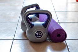 Two 10kg kettlebell weights and purple yoga mat on the floor