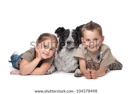 Two kids and a border collie sheepdog in front of a white background