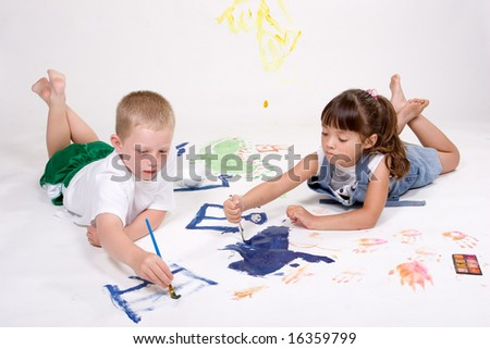 Two kids are painting on large white paper.