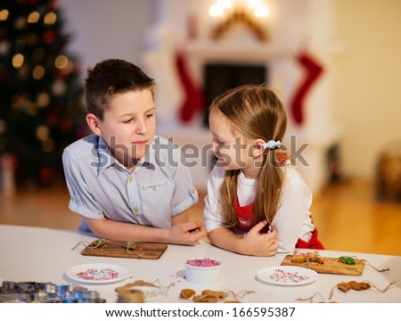 Two kids at home decorating freshly baked Christmas cookies