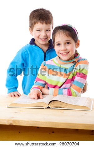 Two kids at the table reading the book together, isolated on white