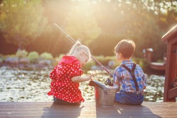 Two kids boy and girl fishing in a river on a wood pontoon