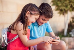 Two kids boy and girl holding smartphone and play games outdoor. Children and gadget addiction concept