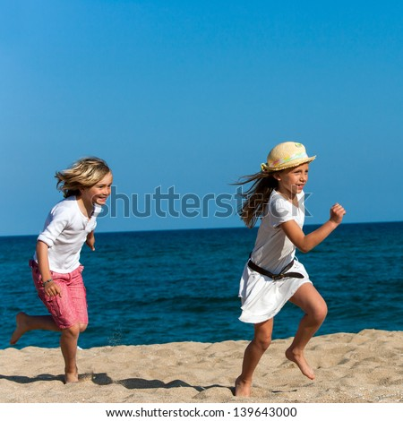 Two kids chasing each other on sunny beach.