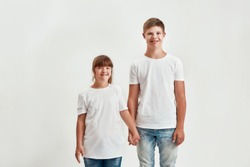 Two kids, disabled boy and girl with Down syndrome smiling at camera, holding each other hands while posing together isolated over white background. Children with disabilities and special needs