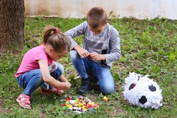 Two kids eat sweets candy on the ground in the garden from a broken pinata toy. Girl and boy squat on the grass and unpacking candies. Play and birthday concept. Close up, selective focus