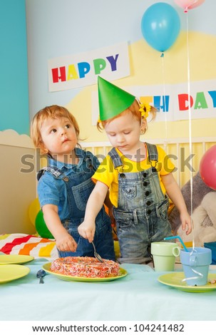 Two kids eating cake on the birthday party - boys and girl
