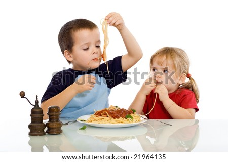 Two kids eating pasta with their hands - isolated