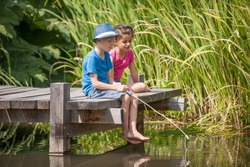 two kids fishing in a river, sitting on a wood pontoon