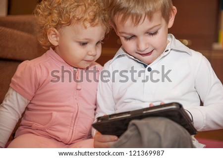 Two kids having fun with a digital tablet