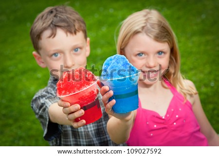 Two kids hold snow cones out to the camera.
