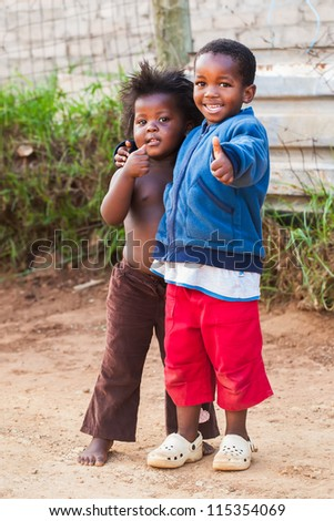 Two kids in the street showing a thumbs up to the photographer.