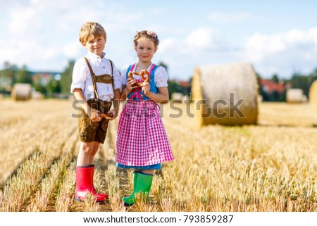 Two kids in traditional Bavarian costumes in wheat field. German children eating bread and pretzel during Oktoberfest. Boy and girl play at hay bales during summer harvest time in Germany ストックフォト ©