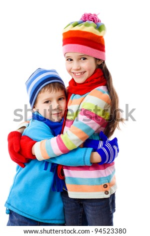 Two kids in winter clothes standing together, isolated on white