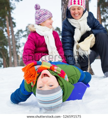 Two kids is sledging with mother in winter-landscape. Focus on the boy.