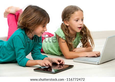 Two kids laying on floor with laptop and digital tablet.
