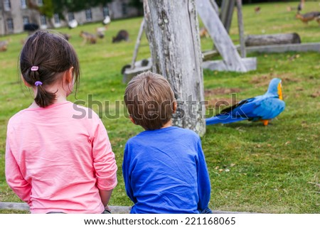 Two kids looking at the park playground with colorful bird and animal statues