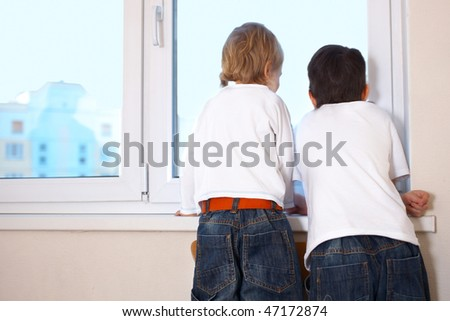 two kids looking at window