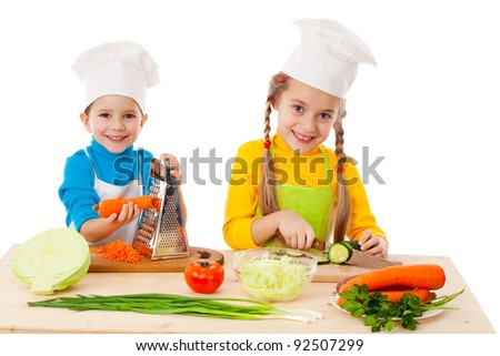 Two kids making salad, cooking the vegetables. Isolated on white