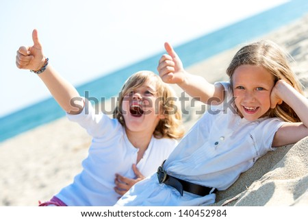 Two kids on beach showing thumbs up symbol together.